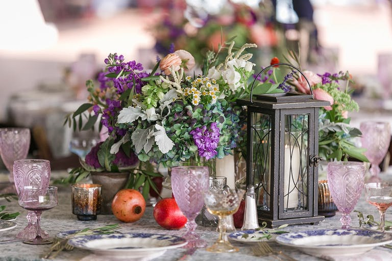 A centerpiece with purple and red florals an sprawling green plants next too candles in lanterns