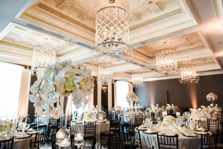 vaulted ceiling in ballroom with tall white orchid wedding centerpieces