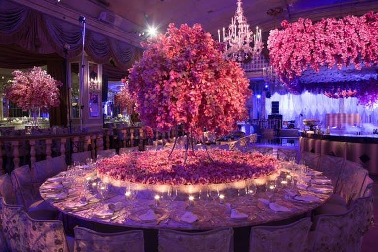 A pink and purple lit room with a massive round table. In the center of the table is a pink tree that extends very tall