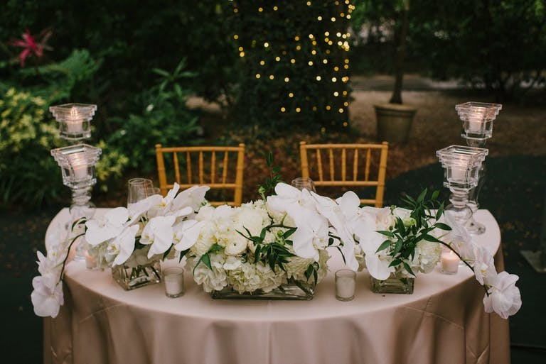 Sweetheart table with pale pink linen, cascading white orchid wedding centerpiece and four glass candle pillars. In the background is greenery and a tree trunk wrapped in string lighting.