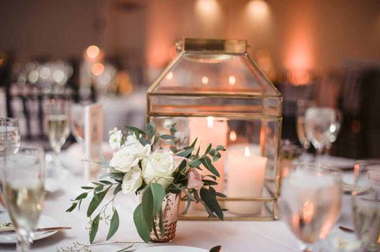 multiple white pillar candles are in the middle of a wide transparent lantern. White florals and greenery are in a votive sized vase interspersed with the lanterns