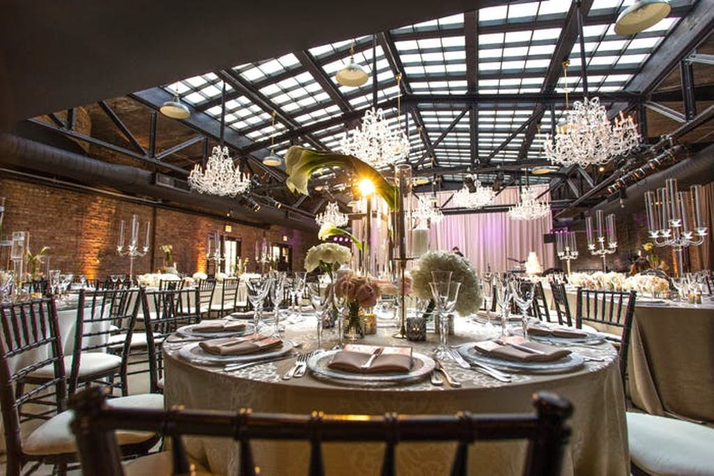 Paned glass ceiling with brick walls and chandeliers.