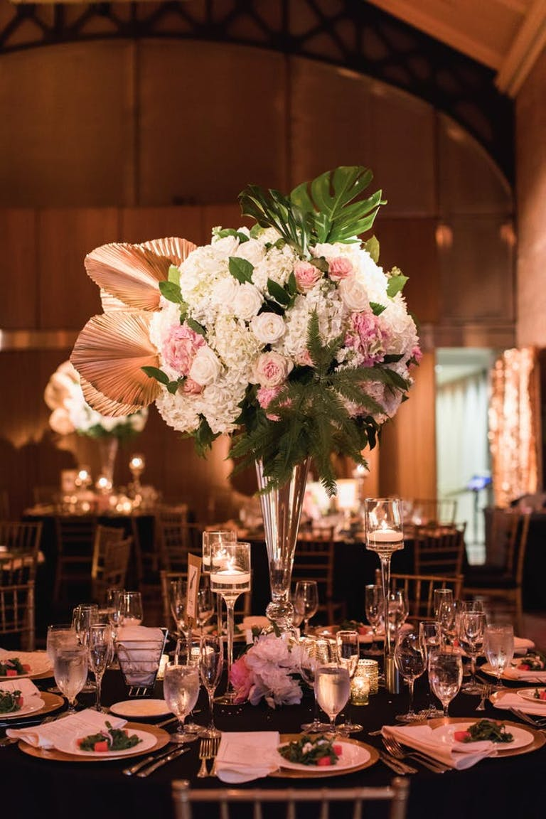 A floral arrangement with gold leaves and pink and white florals sits high above a seating arrangement