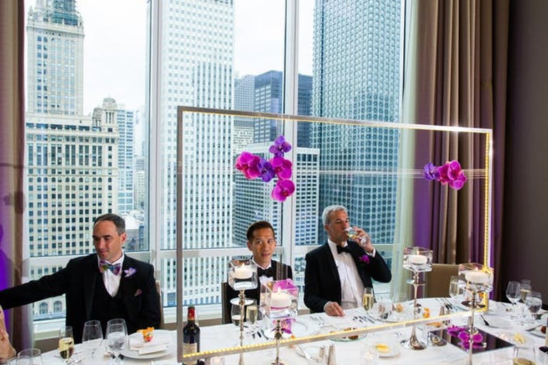 Simple pink and purple orchids hang from a geometric structure on a wedding reception table.