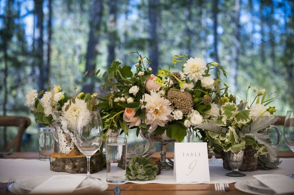 A short floral bouquet atop a table in the woods