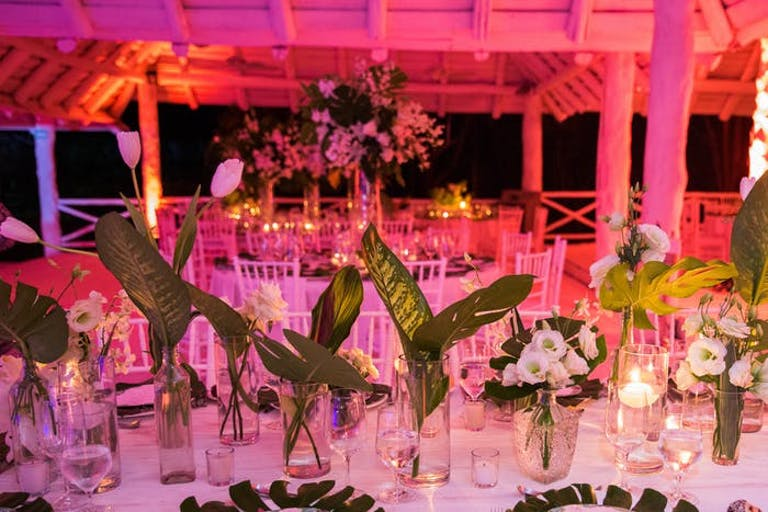 A large gazebo washed in pink light with round tables. Centerpieces are short glasses with leafy greens and small florals