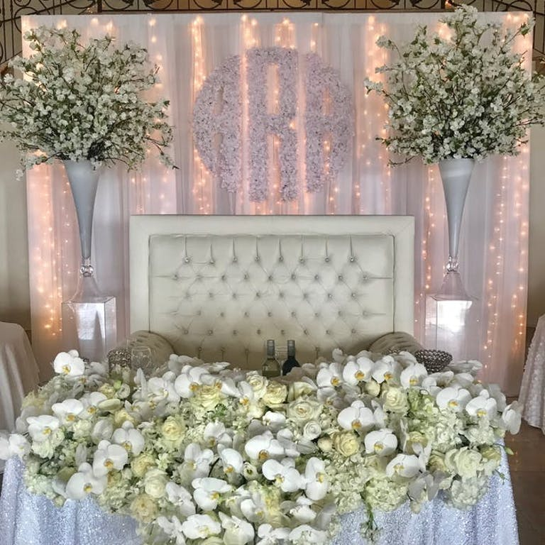 A sweetheart table with a cushioned background with green and white orchid wedding centerpieces