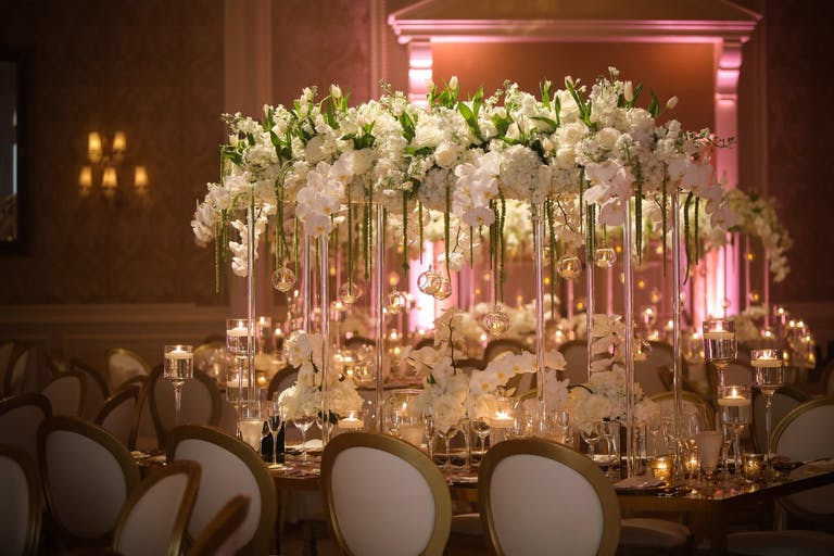 White orchid wedding with centerpiece featuring a bridge of tall, clear vases and an arc of white orchids.