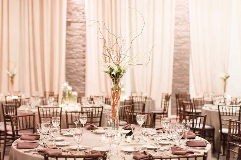 A monochromatic grey room with drapery in the background. The middle ground showcases a twiggy and branchy centerpiece that is tall with white floral accents