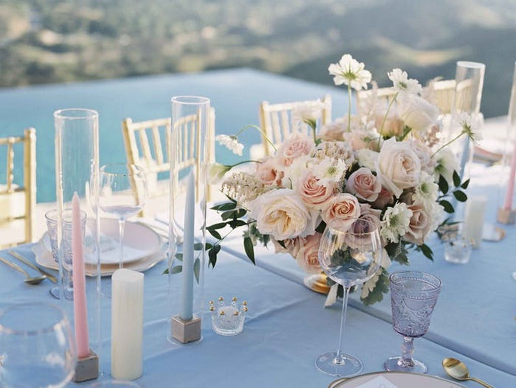 Pink and blue pillar candles juxtaposed with pale pink floral arrangements over looking the pool.