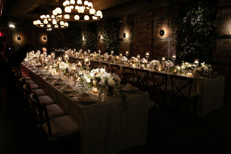 Long table in dark room with candles along the table.
