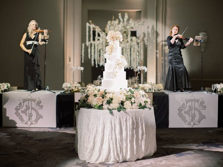 multi-tiered white wedding cake on a center table with musicians on the stage behind it