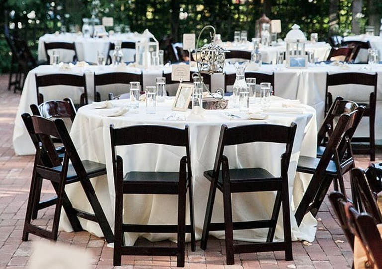 Round tables with black wooden folding chairs. Hanging lanterns are at the center of each table