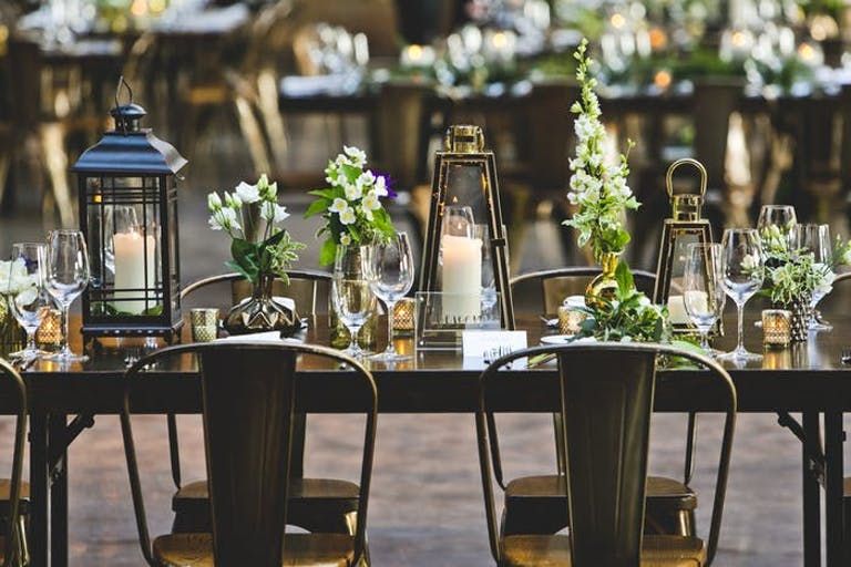 A clean metalic table and chair combination with varrying heights and styles of lantern. Mixed into the lanterns are varying styles and heights of white and green floral arrangements.