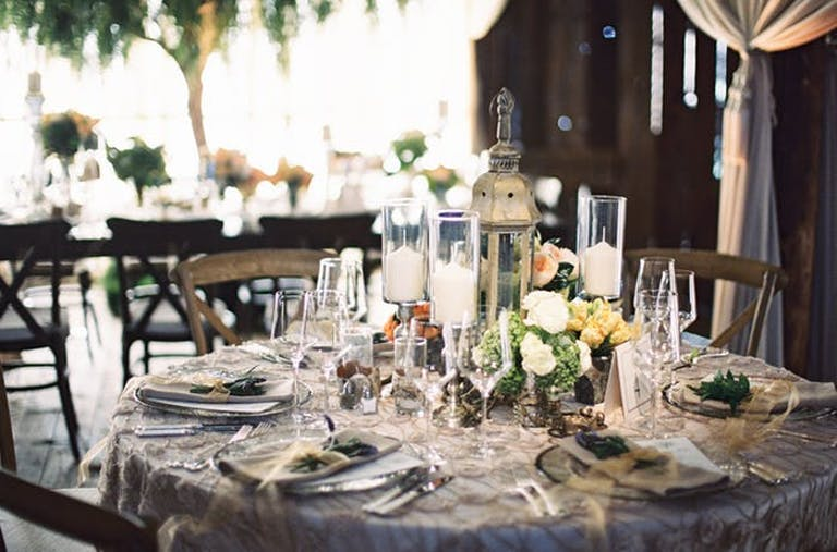 low greenery and white rose arrangements beside raised votive candles and a tall lantern