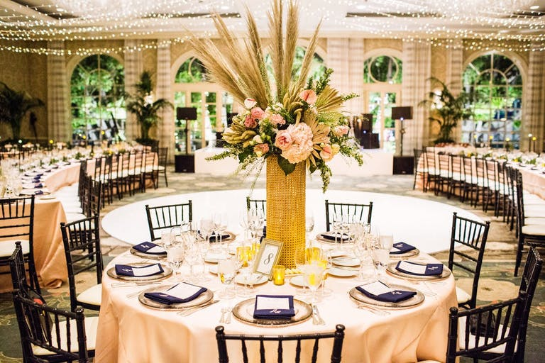 Ballroom with exposed brick and floor to ceiling windows in backdrop. Forefront of photo shows a round banquet table in peach linen with a boho-vibe centerpiece consisting of a wicker vase and pampas grass with blooms.