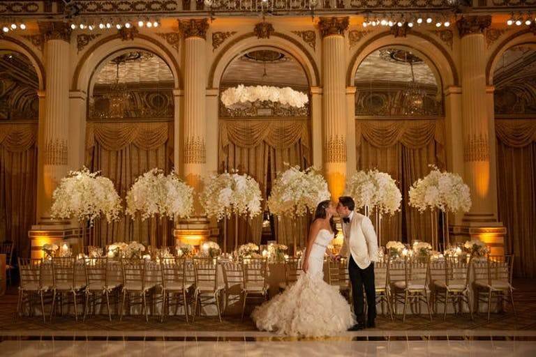 Massive white orchid wedding centerpieces in the background of a couple with archways