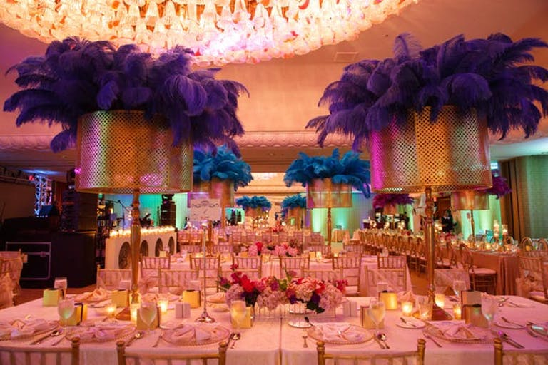 A large room with a light wash of pink and centerpieces in the center of rectangular tables that resemble table lamps with purple feathers coming from the top
