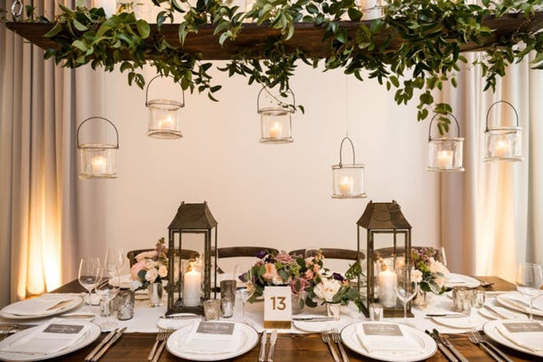 A rectangular table with place settings and low floral arrangements down the center with two lanterns on either side. A rail covered in green leaves is above the table and candles in transparent buckets hang at varying heights