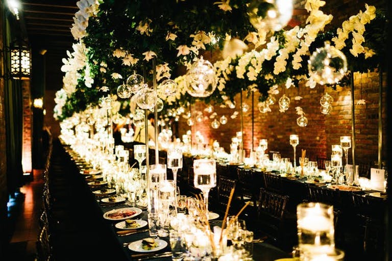 glowing orchid wedding centerpieces down the middle of a long table