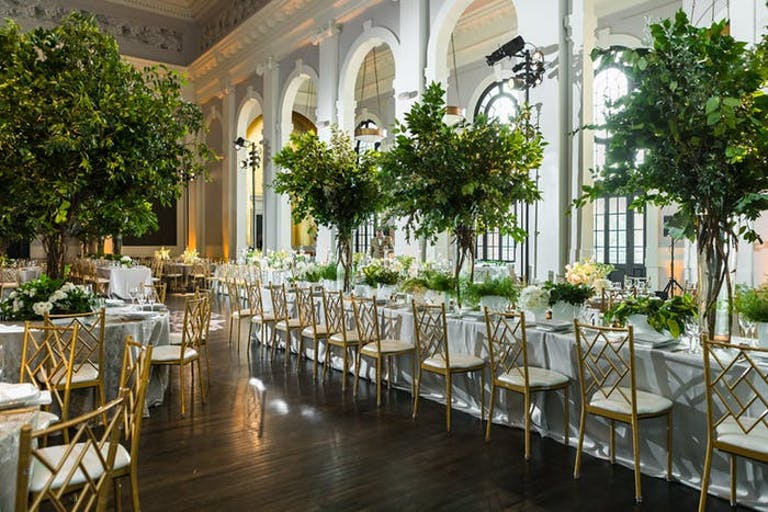 light-filled arched windows beside long rectangular tables with white linens. Trees are planted in the middle scattered through the tables and dark floors