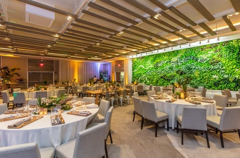 Wooden slats as the ceiling with greenery on a wall. Tabes with white linens