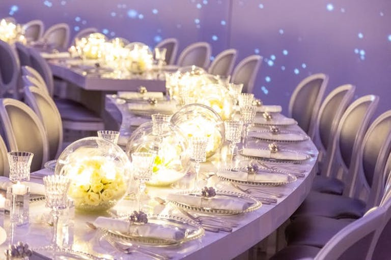 Walls with blue laser beams behind a white circular tables. Transparent globes are filled with gold and yellow lighting and white florals