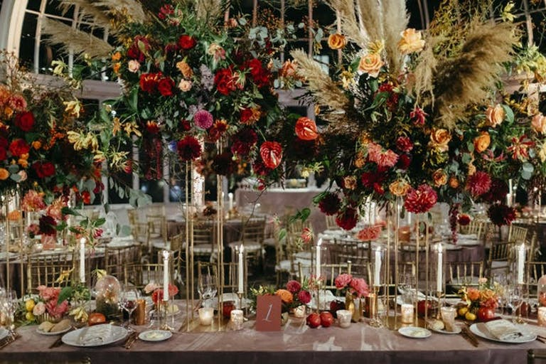 tall multi colored florals lifted with gold stems and white candlesticks