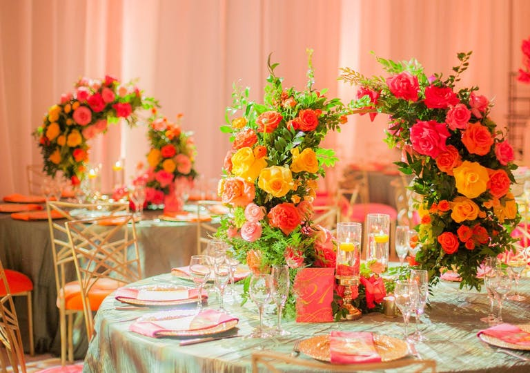 Two banquet tables with pale green linens and pink, yellow, red flower-studded wreath centerpieces against a backdrop of pale pink drapery.