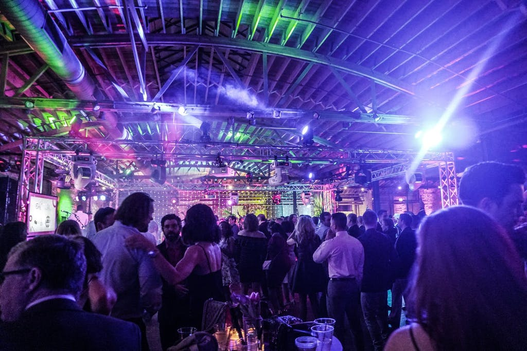 Industrial gala space filled with guests and green and purple uplighting.