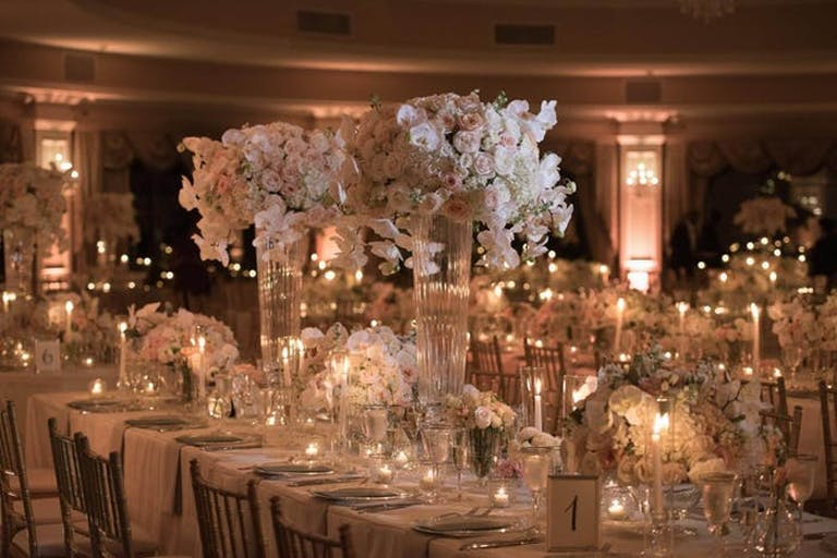 Dimly lit room with warm candles and white spherical white orchid wedding centerpieces