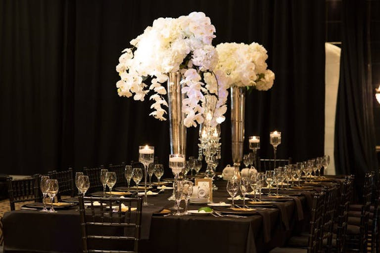 White orchid wedding in candle-lit room.