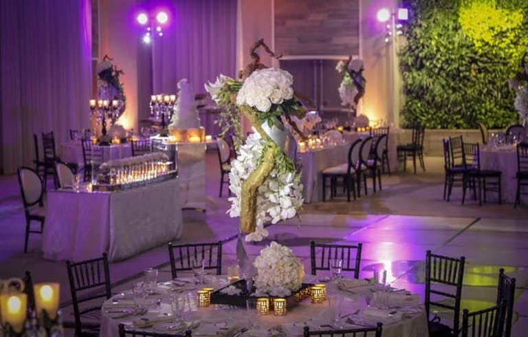 Purple lighting in the background with tall orchid wedding centerpieces