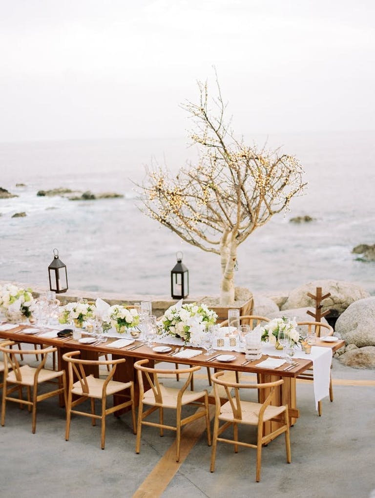 A light wooden rectangular table overlooking choppy water with white linen table runner and low green and white florals. A branchy tree sans leaves sits between the table and the water and metal lanterns hang above the table on a string.