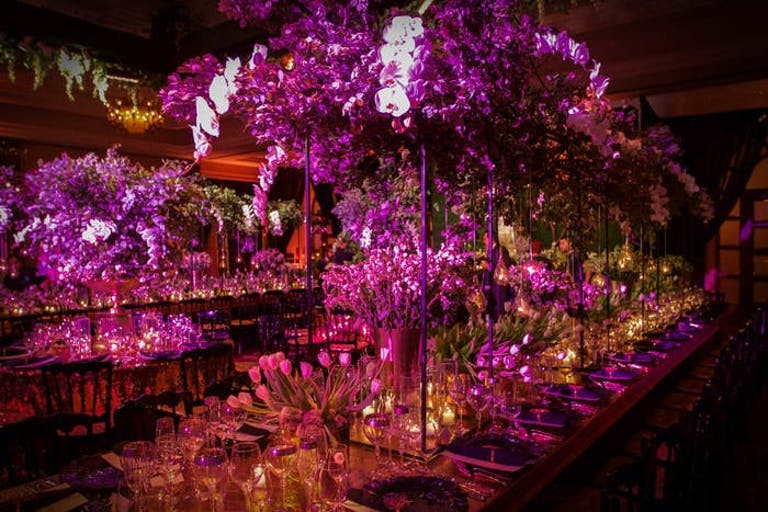 A dimly lit room with candles and pink orchid wedding centerpieces