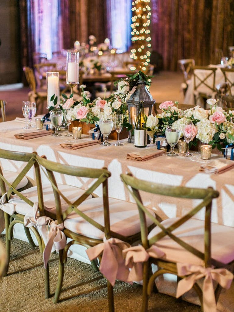 Rectangular table with white linen and wooden chairs surrounding. A lantern is in the middle of the table decor surrounded by pink and white flowers and greenery.