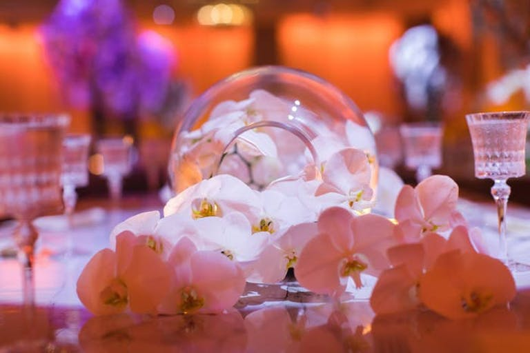 White orchid wedding with small white orchids on a table in a glass bubble