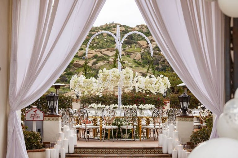 drapery leading to an archway and wedding reception table with white orchid wedding centerpieces
