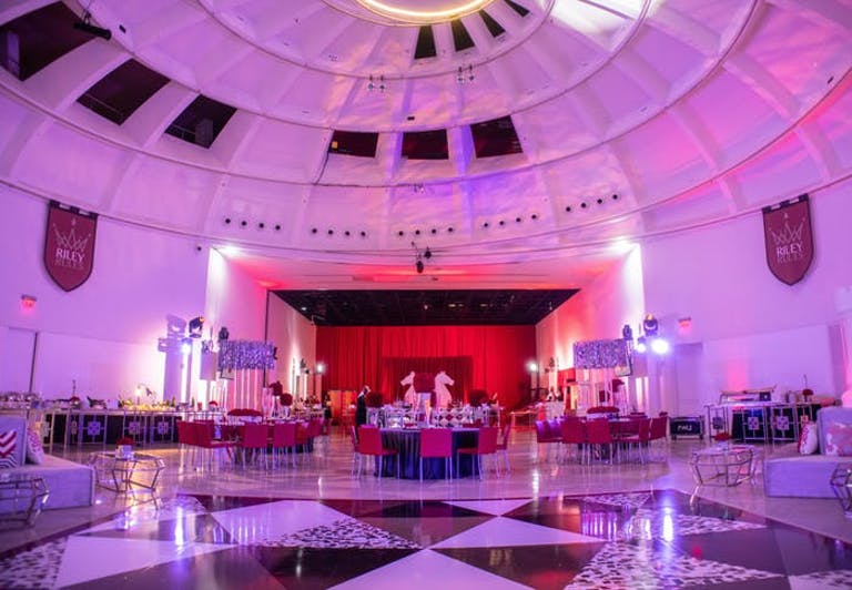 large circular ballroom with pink lighting and a red stage