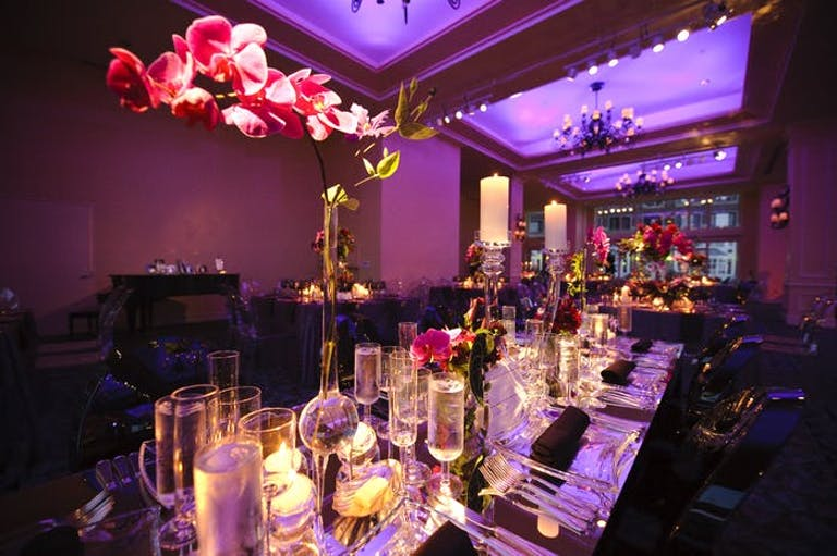 A dimly lit room with purple uplighting, glowing candles, and pink orchid wedding centerpieces.