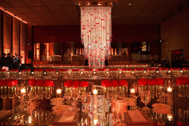 Room with shining table, red glasses and small candles with large chandelier of red and white in the middle giving the room a red hue.