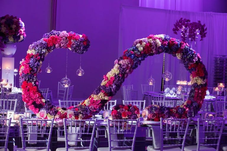 A centerpiece that extends the length of the table. Flowers arranged into an 'S' shape on its back to sit length wise on the table