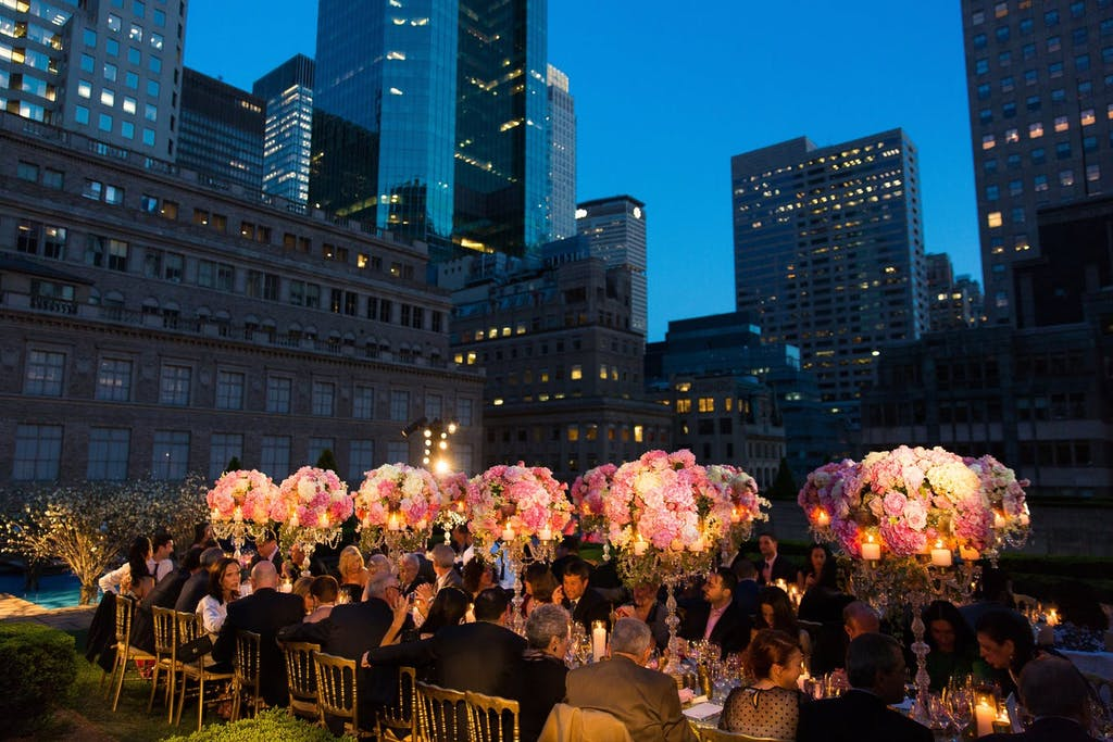 Banquet table with lit up pink floral arrangements at outdoor evening reception in New York City.
