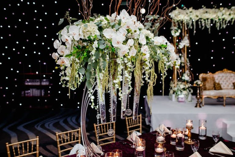 black background with tall overhanging white orchid wedding centerpieces