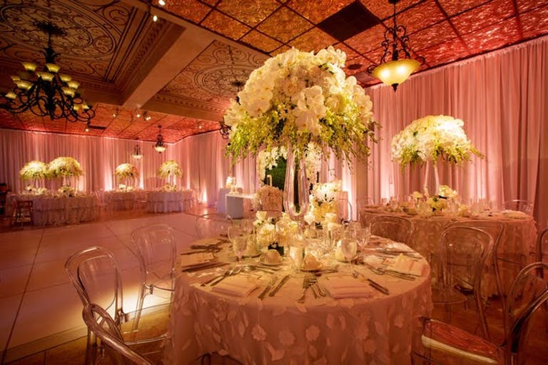 A glowing dimly lit room with yellow and warm white orchid wedding centerpieces.
