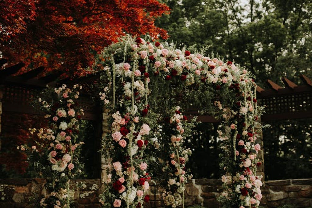 An archway covered in pale pink and white florals mixed with draping greenery