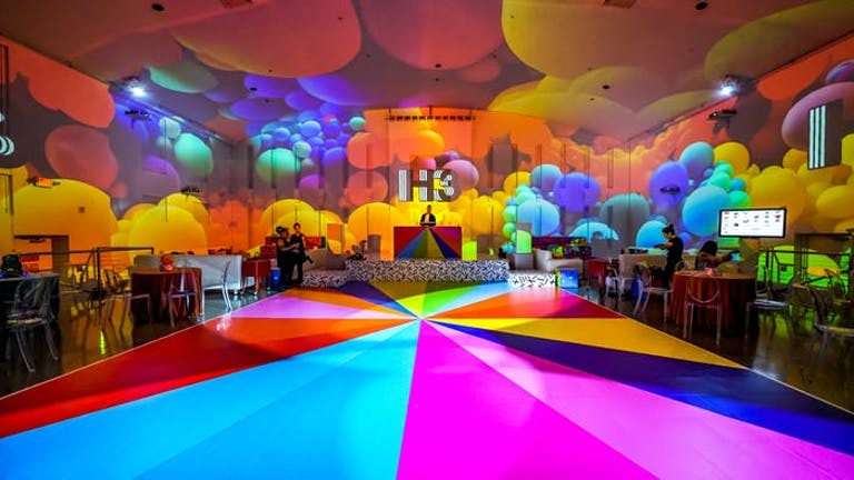 multicolored parachute like flooring with multicolored balloons on ceiling