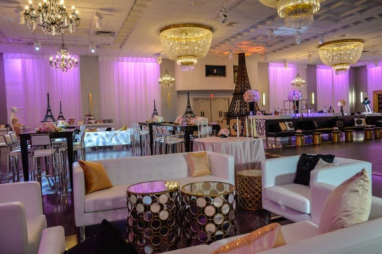 Lounge in the foreground with tables behind them. Walls are lit up purple