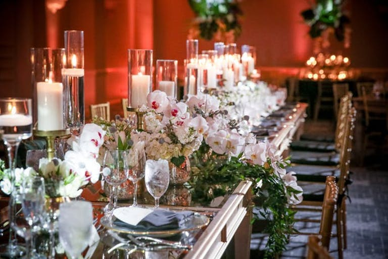 A red backdrop with pillar candles as centerpieces and orchids waterfalling off the table