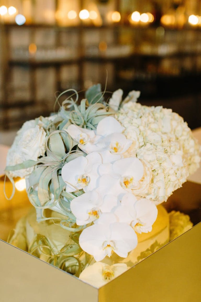 small white orchid wedding centerpieces paired with mild green leaves